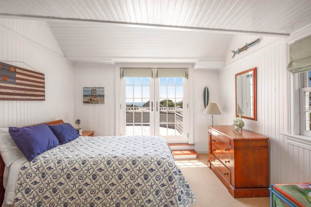 This other look at the bedroom showcases the wooden dresser across from the platform bed with patterned sheets. Image courtesy of Toptenrealestatedeals.com.