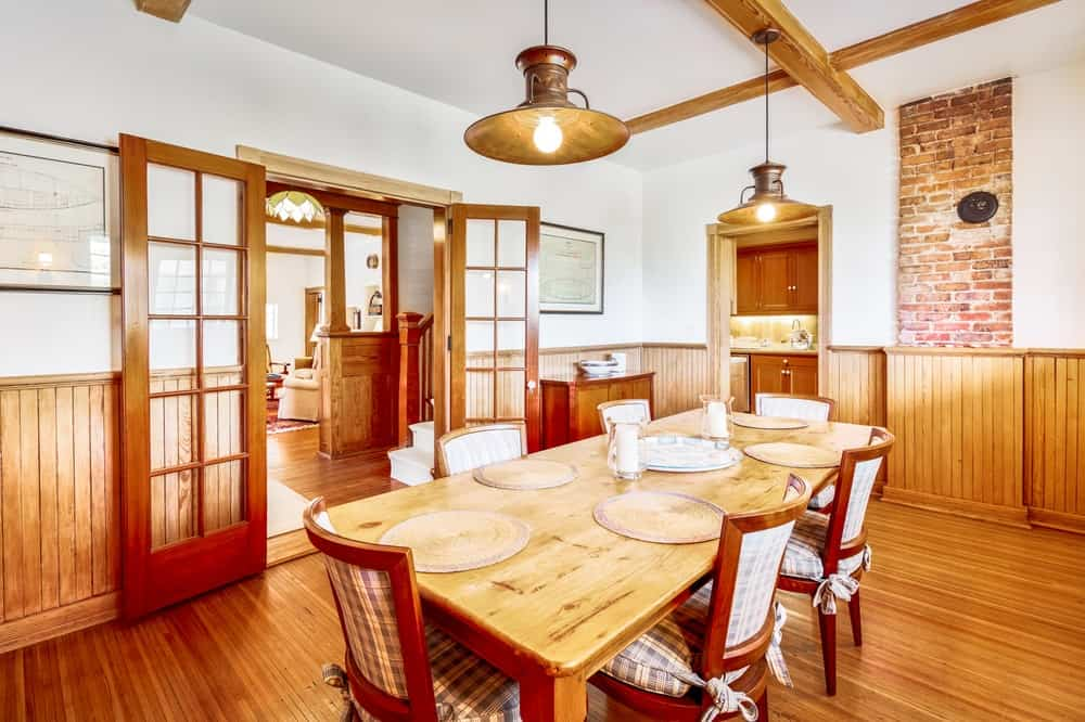 This is the formal dining room with a large wooden dining table that matches well with the hardwood flooring and the exposed beams of the ceiling that hangs a couple of dome pendant lights over the table. Image courtesy of Toptenrealestatedeals.com.