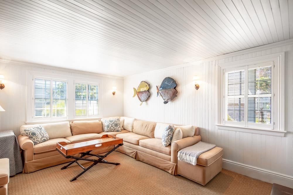 The family room has a large beige L-shaped sectional sofa following the lay of the walls adorned with wall-mounted decors and windows. Image courtesy of Toptenrealestatedeals.com.
