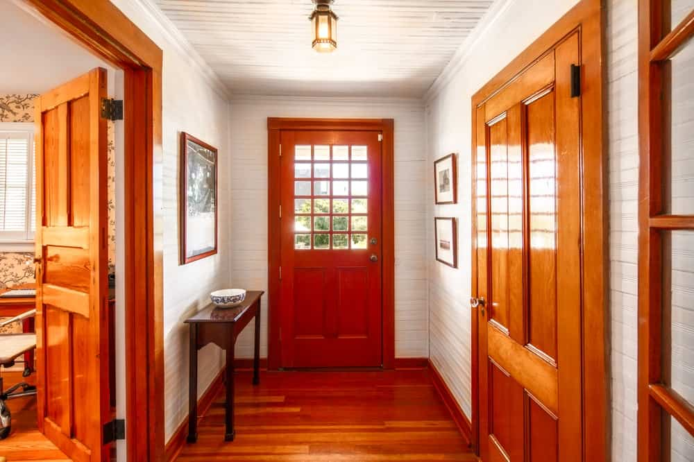 Upon entry of the house, you are welcomed by this simple foyer that has brown wooden doors to match with the hardwood flooring, beige walls and a dark wooden console table. Image courtesy of Toptenrealestatedeals.com.