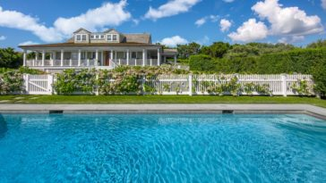 This is a look at the front of the house with a large wrap-around porch festooned with white pillars and railings, dormer windows and a large swimming pool adorned with a lush landscaping. Image courtesy of Toptenrealestatedeals.com.