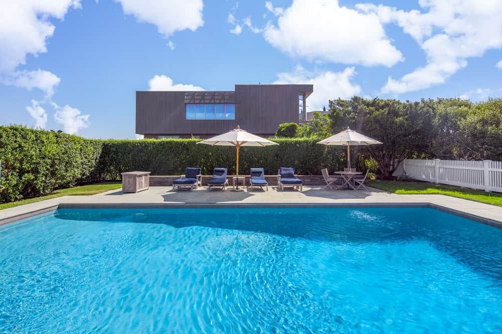 This is the other side of the swimming pool fitted with a couple of relaxing outdoor areas bordered with tall shrub hedges for privacy. Image courtesy of Toptenrealestatedeals.com.