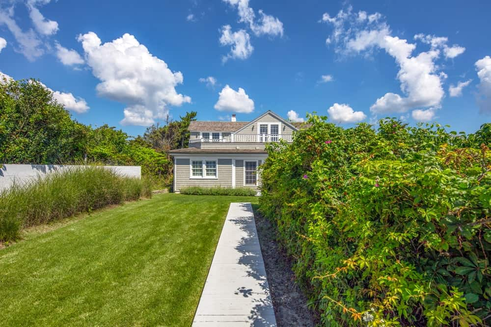 This is a look at the garden of the house with a concrete path and a grass lawn on its side leading to the house. Image courtesy of Toptenrealestatedeals.com.