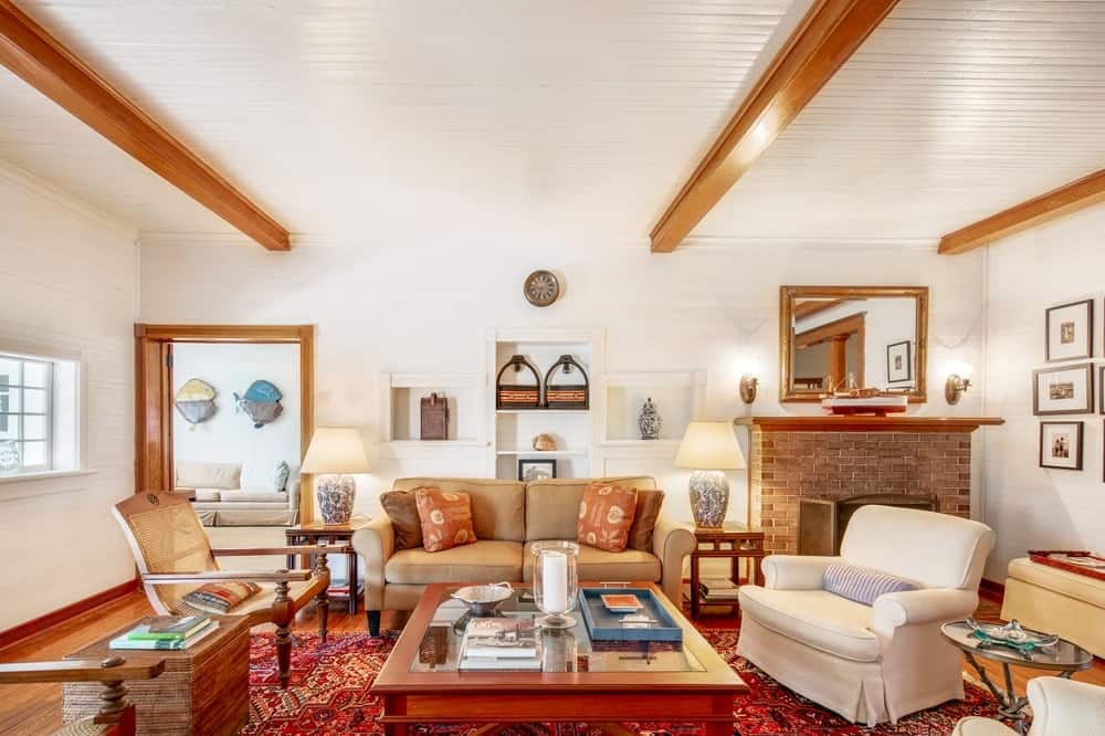 This is the living room with beige walls and ceiling that has exposed beams. These match well with the wooden coffee table surrounded by the sofa set. Image courtesy of Toptenrealestatedeals.com.
