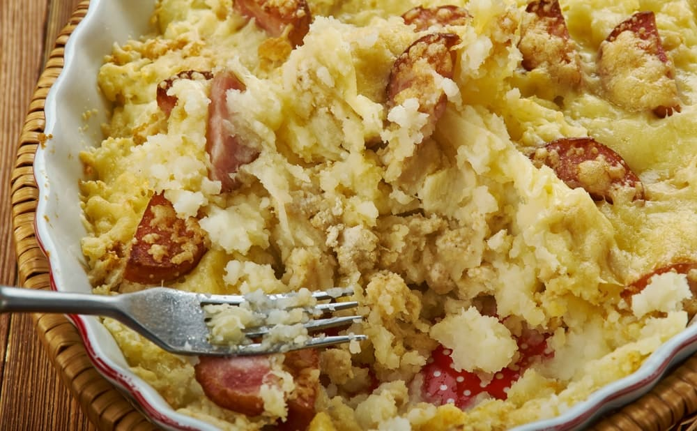 A pan of hash brown casserole with sausages.