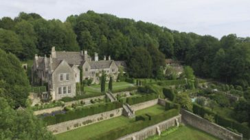 This is an aerial view of the castle-like stone manor that is surrounded by lush landscaping that is shorn, terraced and has mature trees and shrubbery. Image courtesy of Toptenrealestatedeals.com.