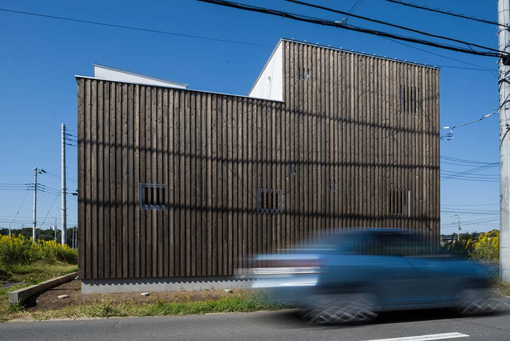 This is a side view of the house with a patterned and textured exterior wall fitted with small windows that also has the same patterned panels of the exterior walls.