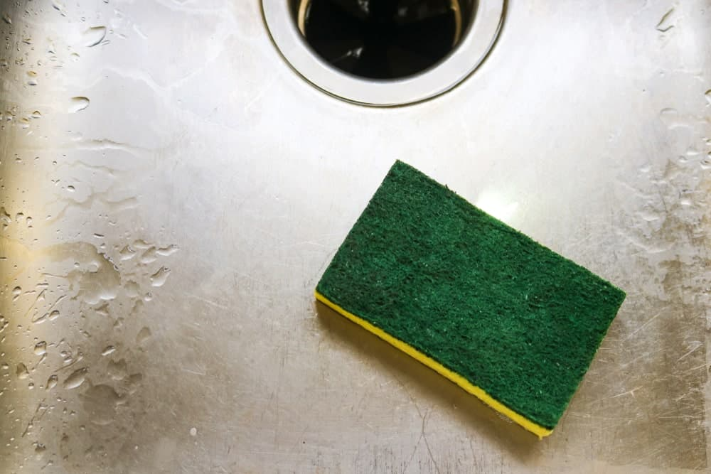 A green and yellow dish sponge on a stainless steel sink.