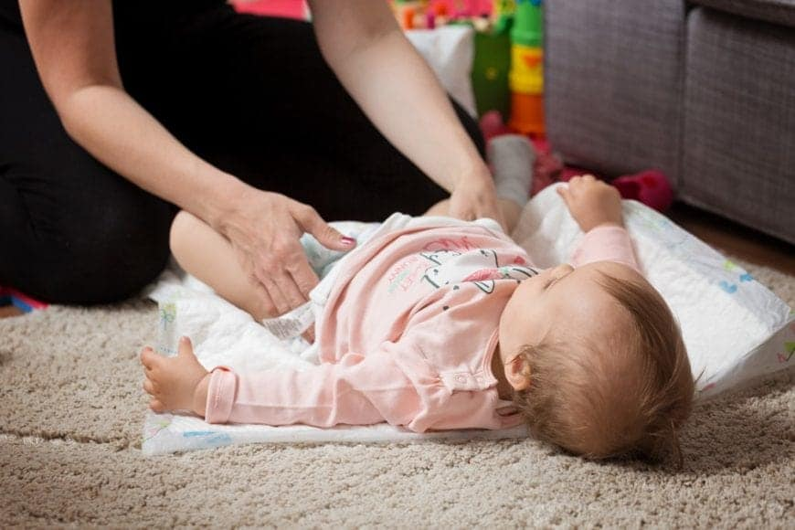 Mom changing her baby's diaper on a carpet.