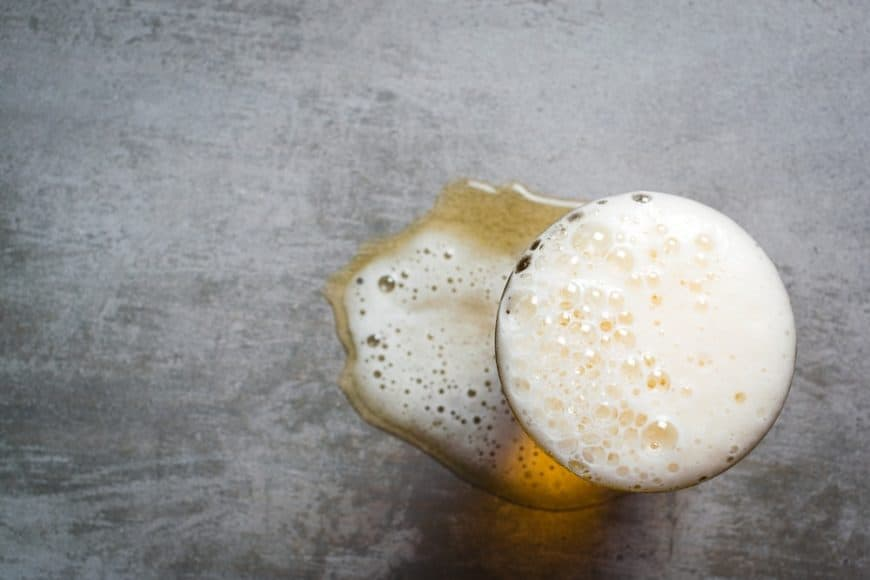 Top view of a glass of beer against a concrete background.