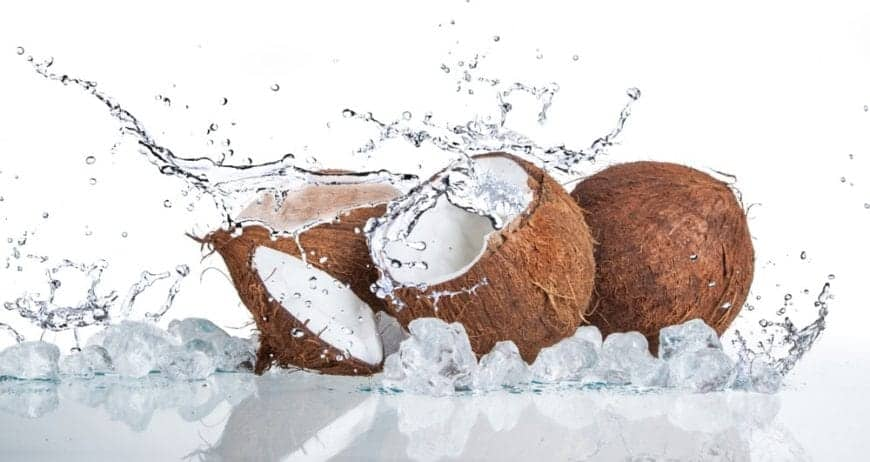 Coconut fruits with splashes of water and oil against a white background.