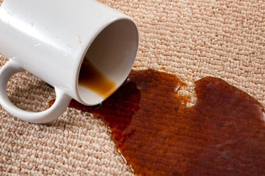 Coffee spilling out from a mug on a carpet.
