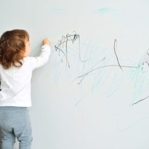 A toddler playing with crayons on the wall.