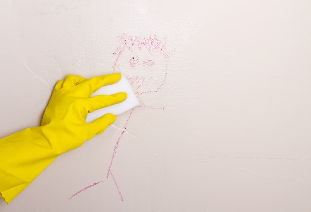A gloved hand scrubbing the crayon drawing off the wall.