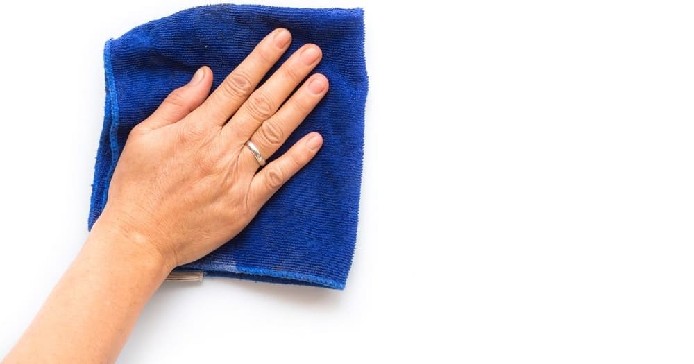 A hand wiping the white wall with a rag.