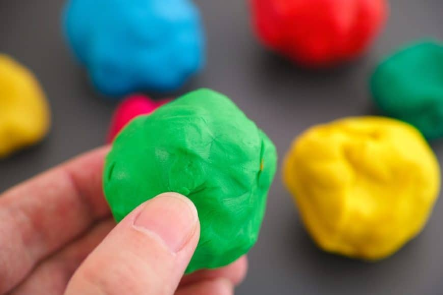 A hand holding a green playdough against blurred background of multicolored playdoughs.
