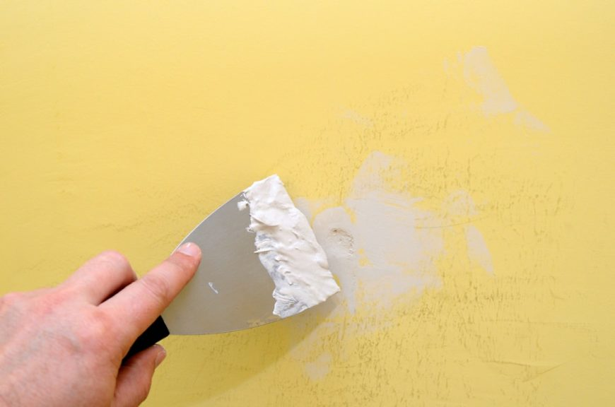 A close look at someone removing the poster putty from the wall.