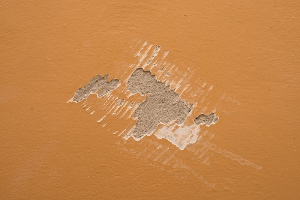 A close look at a wall with a spot of scraped paint.