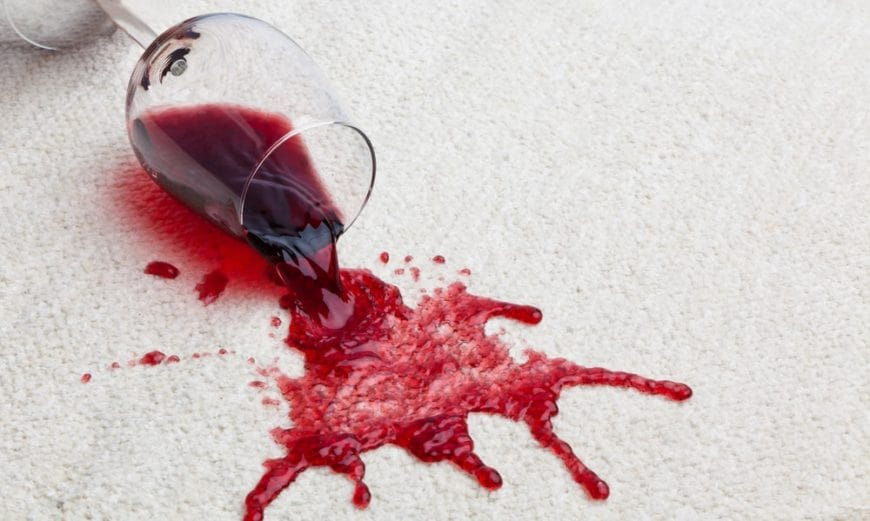 Red wine spilling out from a wine glass on a beige carpet.