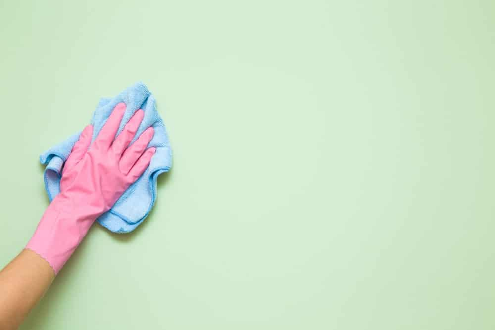 Nane yeşili duvarı silen eldivenli bir el.