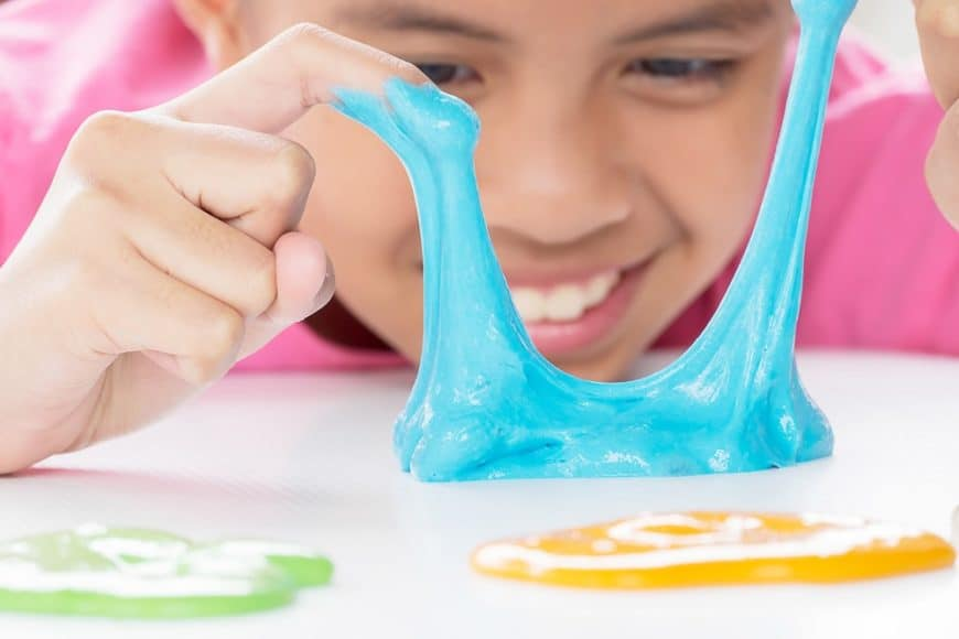 A kid playing with multi-colored slime.