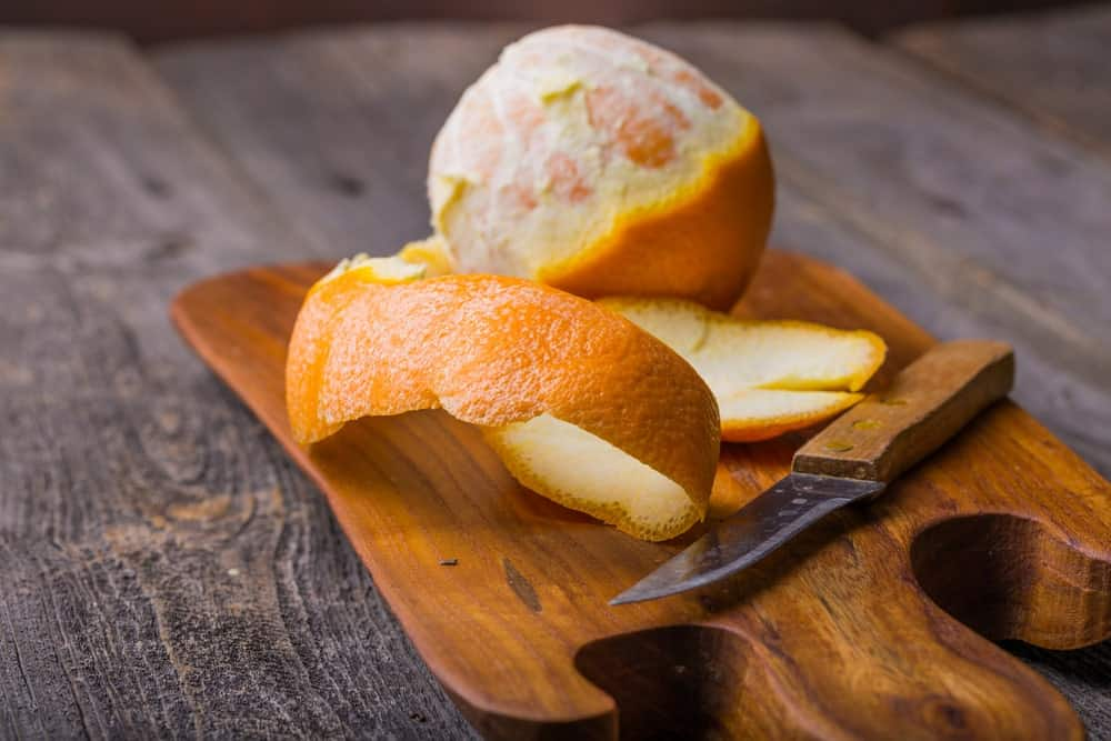 A peeled orange on a wooden chopping board.