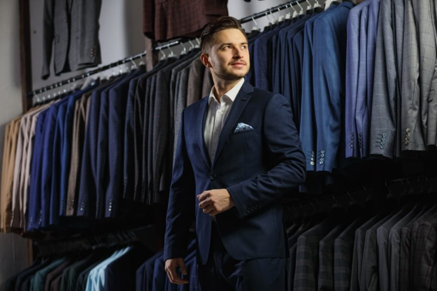A man trying on a navy blue suit in a suit store with racks of suits.