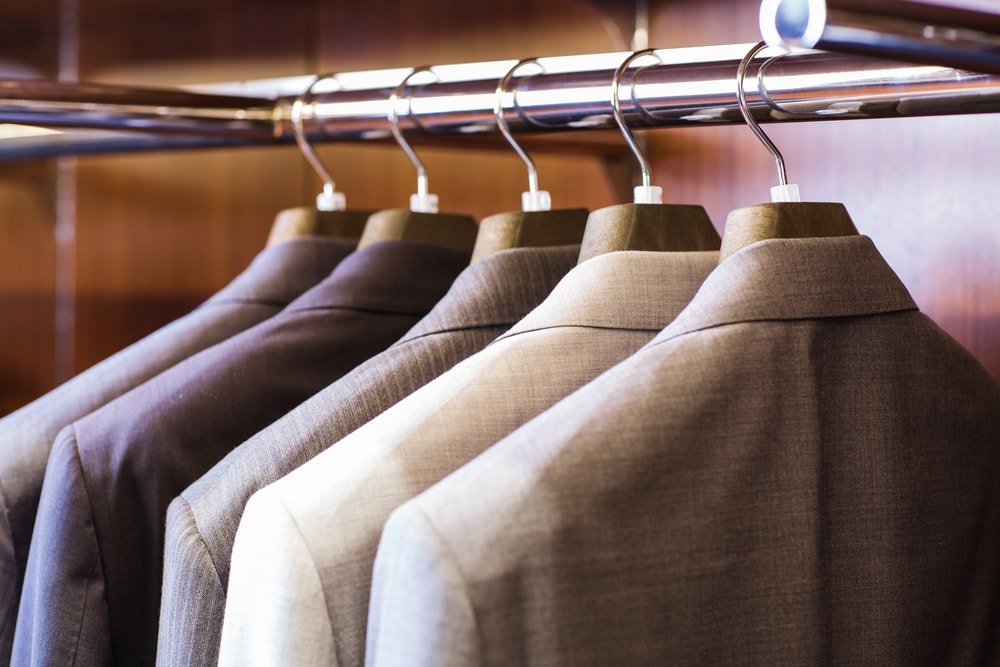 A row of suit jackets stored in a closet.