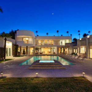 This is a view of the backyard of the mansion with a large swimming pool that pairs well with the warm glow of the exterior walls with large glass walls and windows. Image courtesy of Toptenrealestatedeals.com.