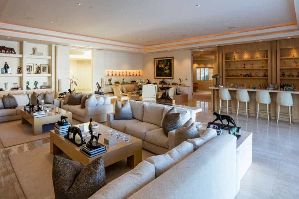 This is a close look at the living room that has a beige sofa set to pair with the wooden coffee table. These pair well with the beige walls and wide beige ceiling. Image courtesy of Toptenrealestatedeals.com.