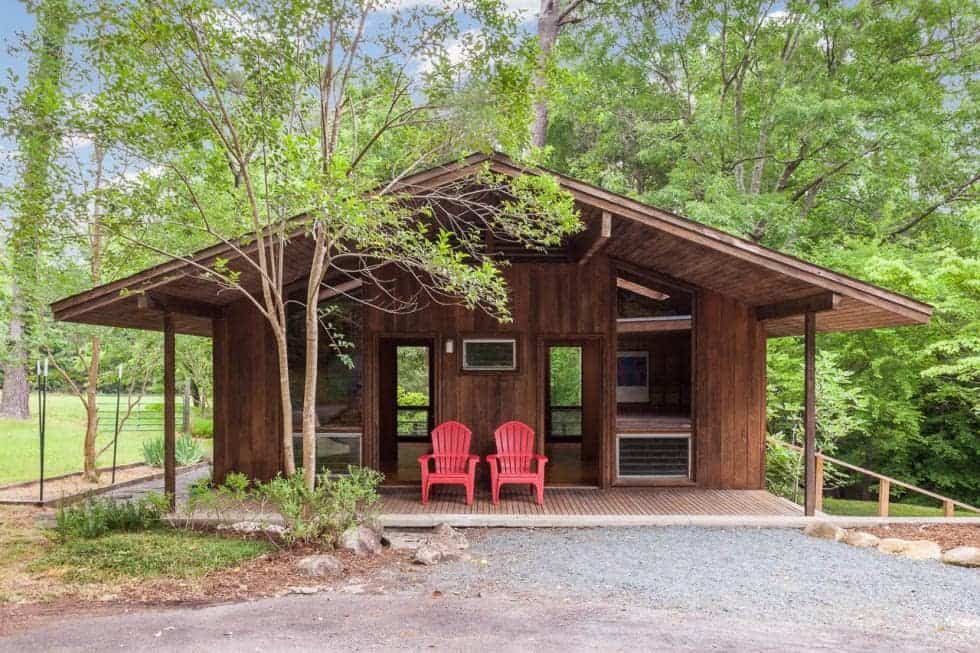 The back of the house has lush landscaping of trees and shrubs to contrast the dark wooden tone of the house exterior fitted with a couple of lounge chairs to better enjoy the landscape scenery. Image courtesy of Toptenrealestatedeals.com.