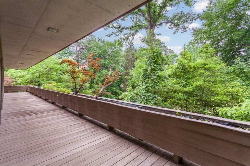 This is the long a nd spacious balcony with a wooden deck flooring and planters on its railings. Image courtesy of Toptenrealestatedeals.com.