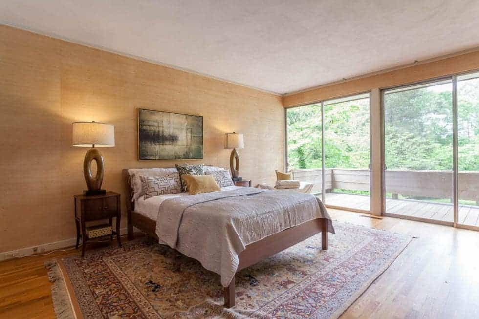 The bedroom has large glass walls that ring in natural lighting for the bed that is flanked by bedside drawers and table lamps and topped with a painting. Image courtesy of Toptenrealestatedeals.com.