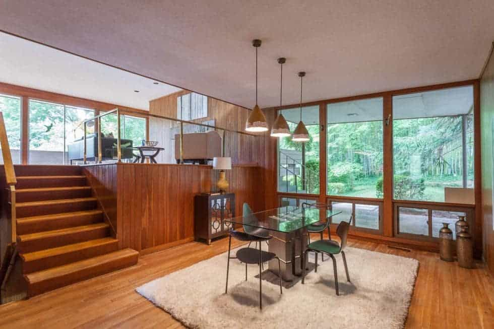 A few steps from the elevated living room is the dining area with a rectangular glass-top dining table surrounde dby modern chairs and topped with pendant lights. Image courtesy of Toptenrealestatedeals.com.