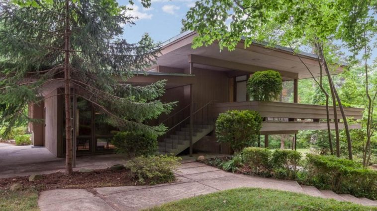 This is the front of the house with a dark brown tone to its exteriors that make it stand out against the surrounding lush landscaping. Image courtesy of Toptenrealestatedeals.com.