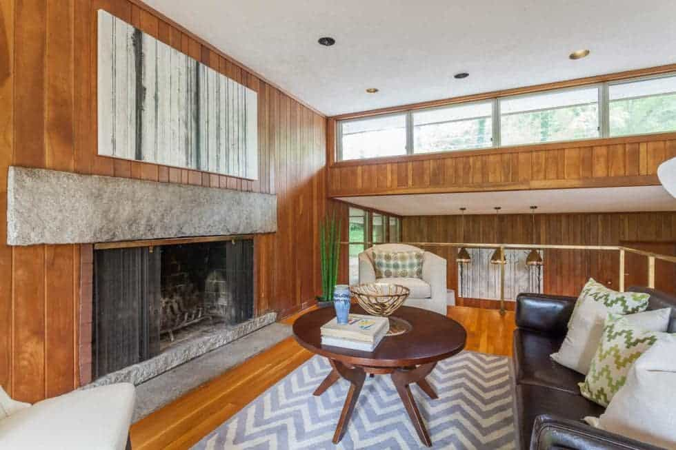 The living room has a large fireplace across from the black leather sofa and wooden round coffee table on a patterned area rug. Image courtesy of Toptenrealestatedeals.com.