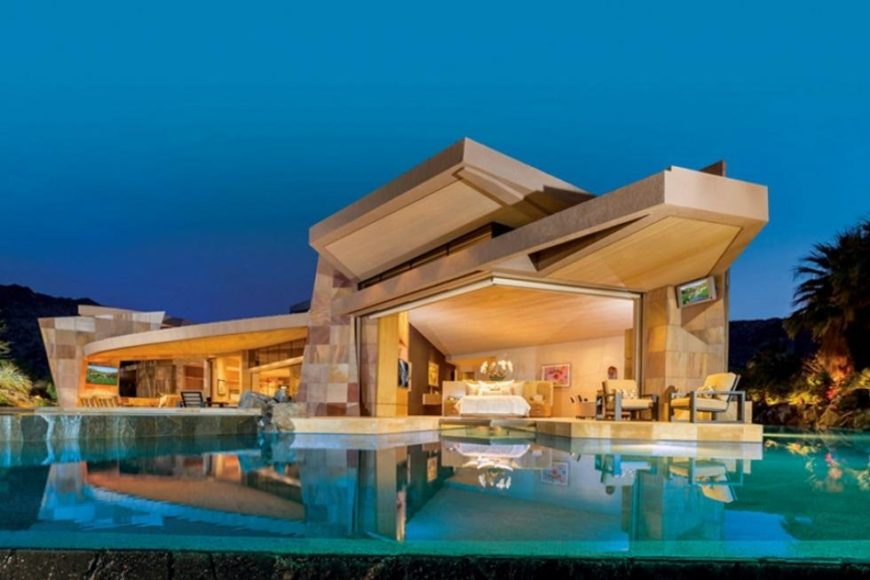 This is a view of the house from the backyard pool. You can see here that the beige exteriors of the house are glowing warmly from the interior lights. Image courtesy of Toptenrealestatedeals.com.