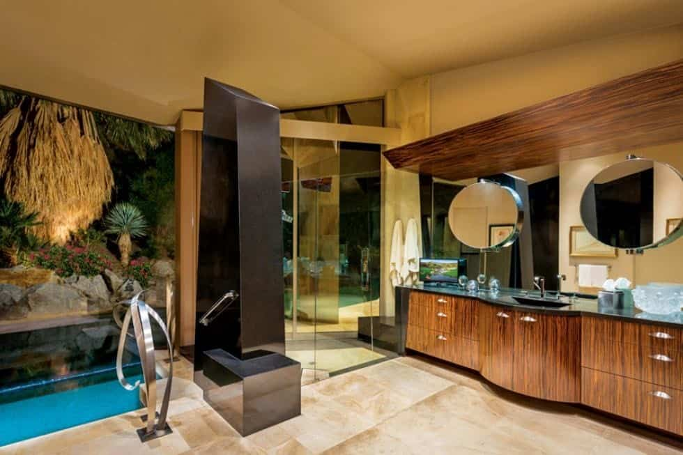 This is the elegant bathroom with glass elements on its walls and mirrors to pair with the wooden vanity and beige tones of the flooring tiles and ceiling. Image courtesy of Toptenrealestatedeals.com.