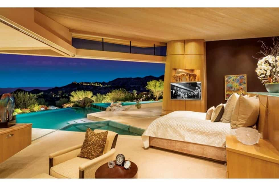 This is the primary bedroom with a large curved opening across from the bed that has a direct access to the pool area. Image courtesy of Toptenrealestatedeals.com.