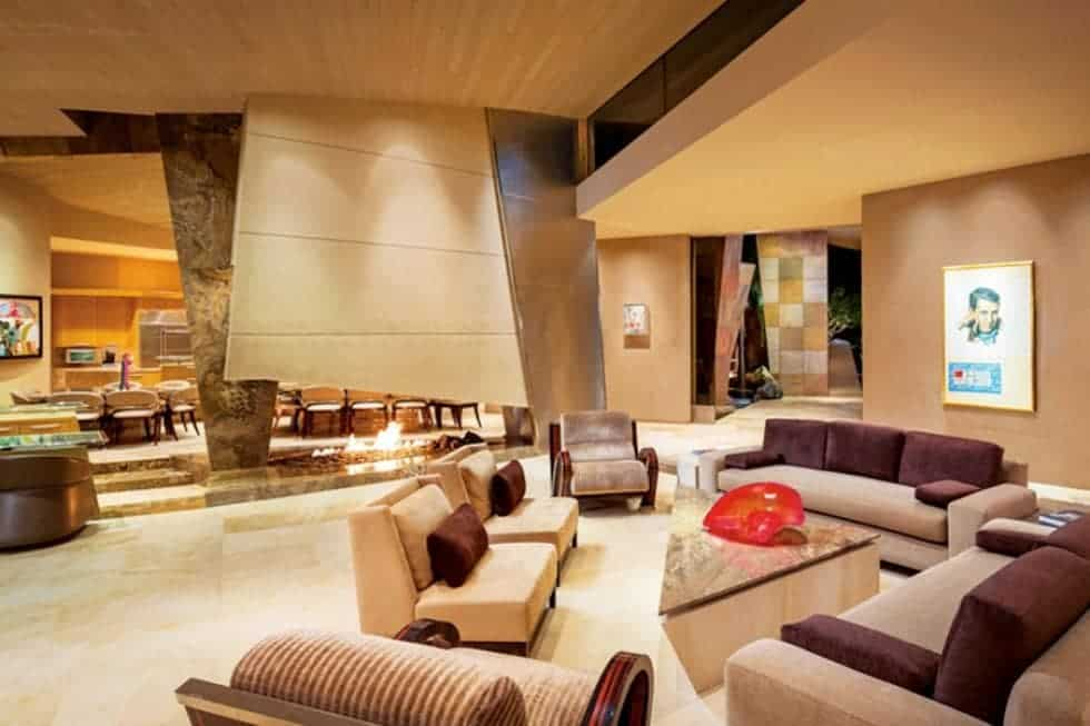 This is the spacious and airy living room with a tall ceiling, a unique modern fireplace and a set of sofas all in a beige tone. Image courtesy of Toptenrealestatedeals.com.