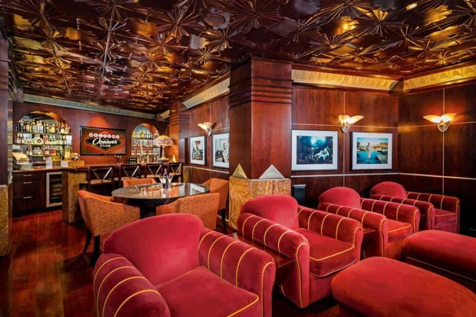 This is the London-style pub replica of the house with elegant wooden panels on its ceiling, pillars and walls. These pair well with the comfortable red cushioned armchairs and wall sconces. Image courtesy of Toptenrealestatedeals.com.