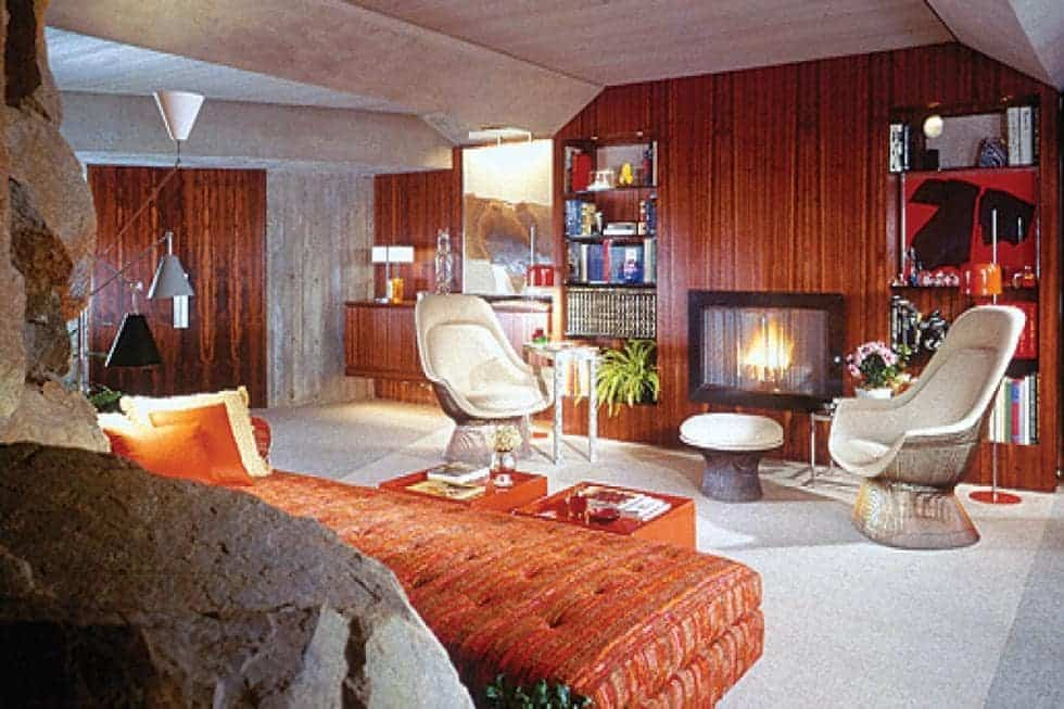 This is the den with a fireplace on the far wall across from the sofa that matches the tone of the wood-paneled walls. Image courtesy of Toptenrealestatedeals.com.
