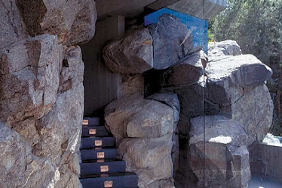 This is a look at the main entrance of the house with a set of steps adorned by large rock boulders and a main door that has an earthy tone. Image courtesy of Toptenrealestatedeals.com.