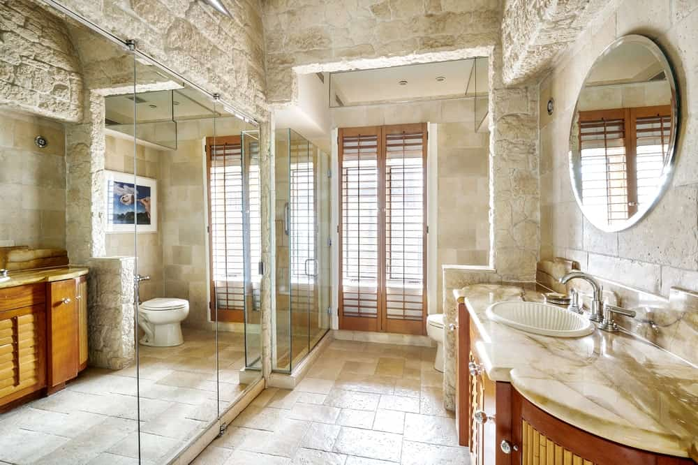 The bathroom has a large walls of mirrors across from the vanity beside the toilet. Image courtesy of Toptenrealestatedeals.com.