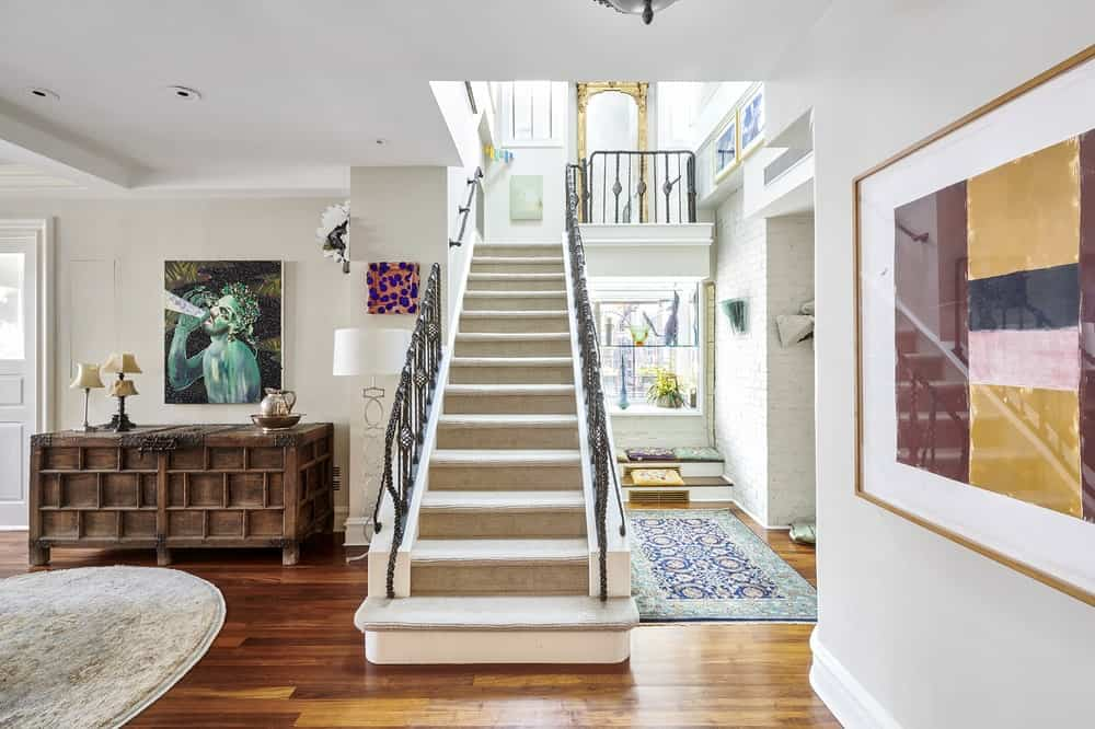 Upon entry of the penthouse, you are welcomed by this foyer with hardwood flooring and a staircase. Image courtesy of Toptenrealestatedeals.com.