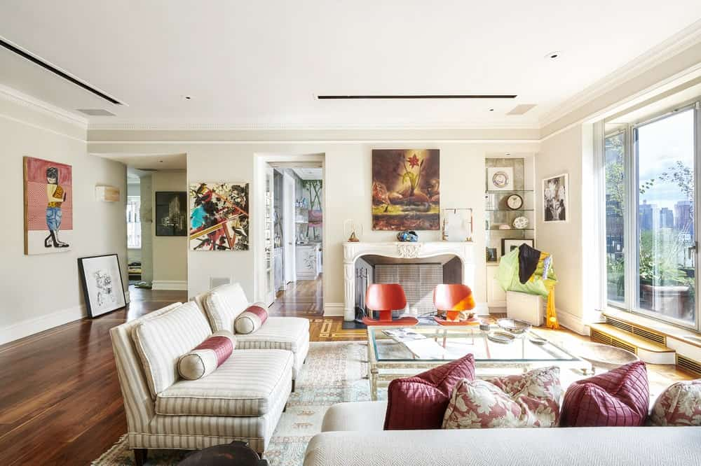 This is the bright living room with beige sofas and fireplace at the far end with a painting. Image courtesy of Toptenrealestatedeals.com.