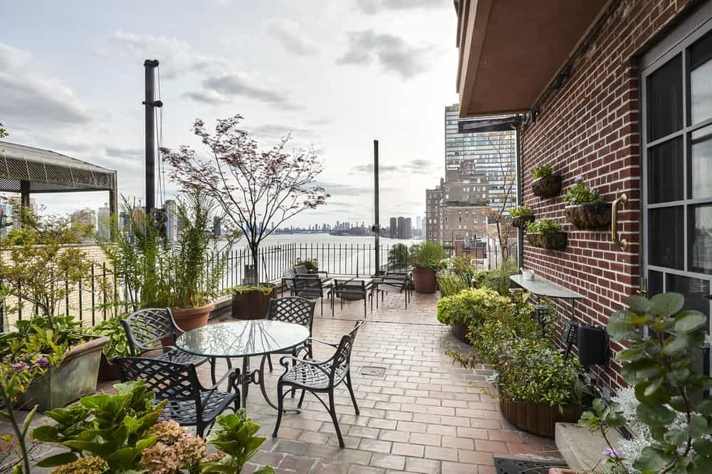 This is the wrap-around terrace with a brick walkway to pair with the brick walls. These are then adorned with various potted plants that serve as background for the outdoor dining area. Image courtesy of Toptenrealestatedeals.com.