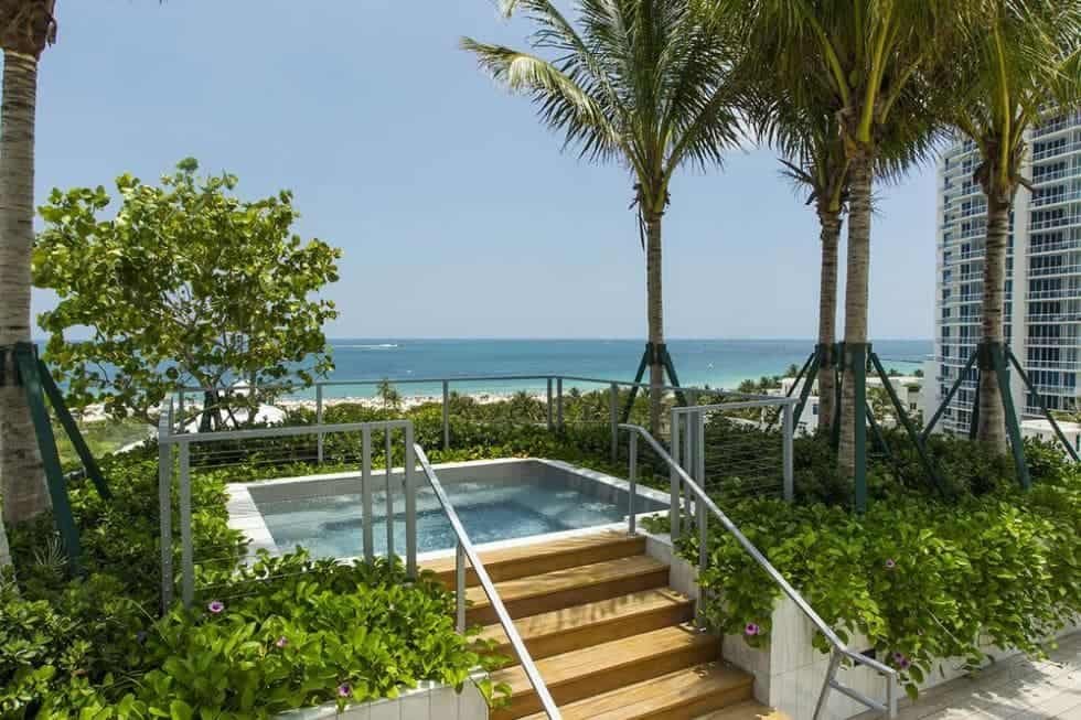This section of the large terrace has a spa-type pool surrounded by tropical shrubs and trees and has a sweeping view of the beach beyond. Image courtesy of Toptenrealestatedeals.com.