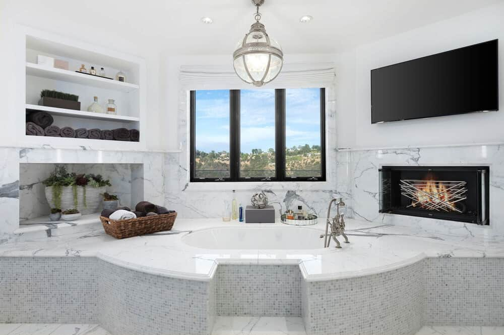 This is the bright white bathroom with a bathtub under the window. On the sides of the bathtub are built-in structures like shelves, a fireplace and a wall-mounted TV. Image courtesy of Toptenrealestatedeals.com.