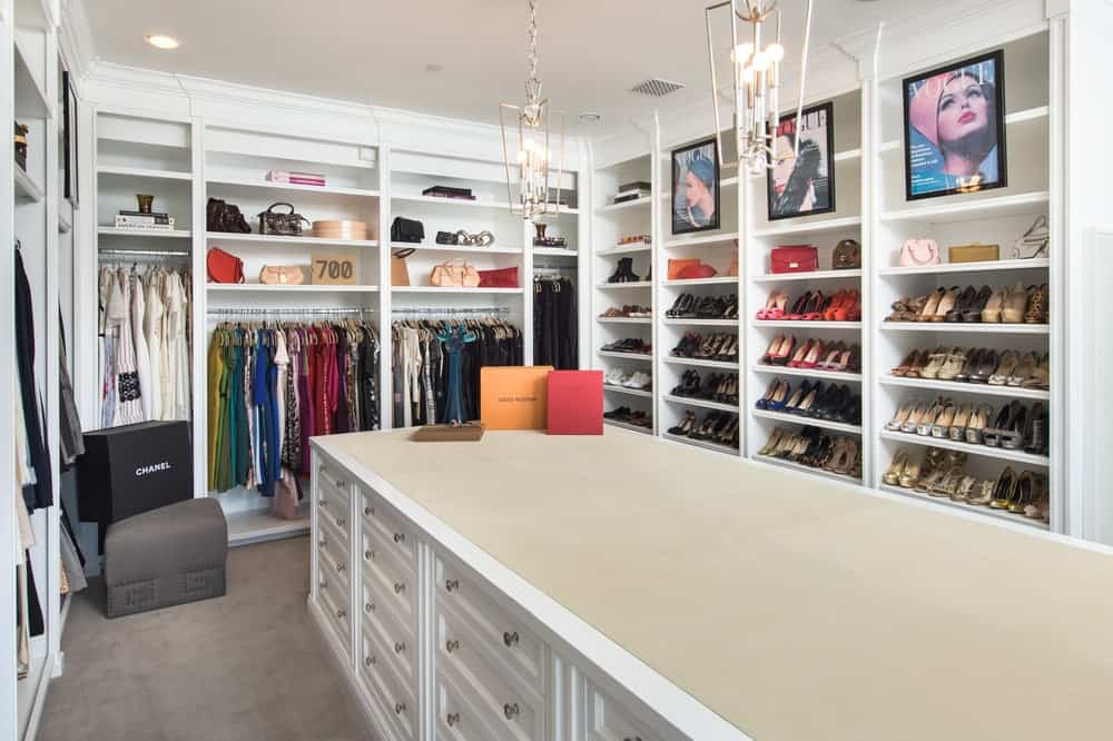 This is the walk-in closet with bright white wooden structures built into the walls surrounding the large island cabinet in the middle. Image courtesy of Toptenrealestatedeals.com.